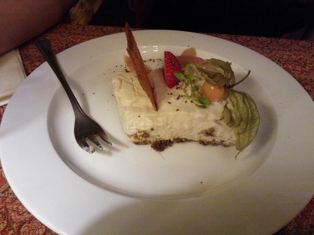 Tuorejuustokakku mustalla leipäpohjalla ja raparperia