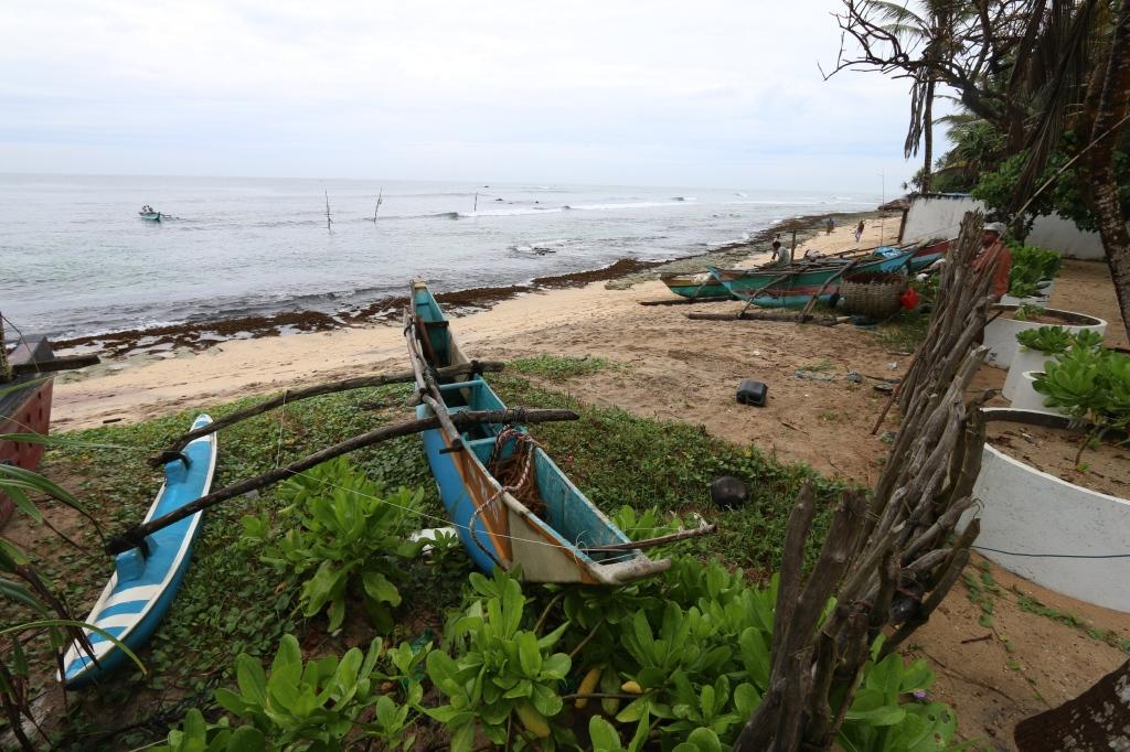 Piha-aidan takana näyttää tältä. Kalastajaveneet on tosiaan aivan siinä takana ja ranta samaten. Tarkkasilmäiset löytää Jayasenan vahtimassa kalastajien puuhia.