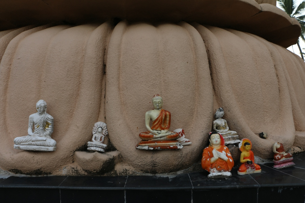 Small Buddha statues at the foot of the big one